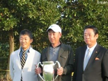 株式会社ゴルフパートナー執行役員の川崎康史氏(左)と、公益社団法人日本プロゴルフ協会の井上建夫副会長(右)に挟まれ笑顔を見せた若杉和浩。賞金100万円が贈られた(撮影:ALBA)