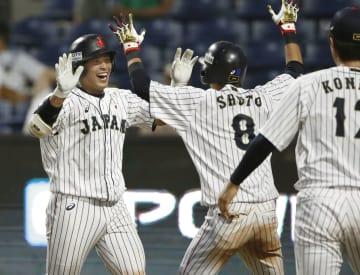 日本―ベネズエラ 8回、勝ち越し3ランを放ち、チームメートに迎えられる堀内(左端)=バランキジャ(共同)