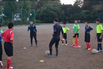 サッカー部の活動日に外部講師から技術指導を受ける生徒ら=つくば市東
