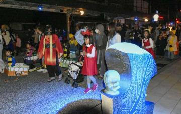 ライトアップされた妖怪のブロンズ像(手前)が並ぶ通りを練り歩く参加者=27日夜、鳥取県境港市