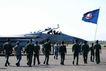 日米共同訓練に参加する米軍のF15戦闘機を出迎える自衛隊員=27日午前、新富町・新田原基地