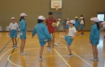 アウンソーモーさん(中央)とチンロンを楽しむ児童たち=龍ケ崎市立馴馬台小体育館