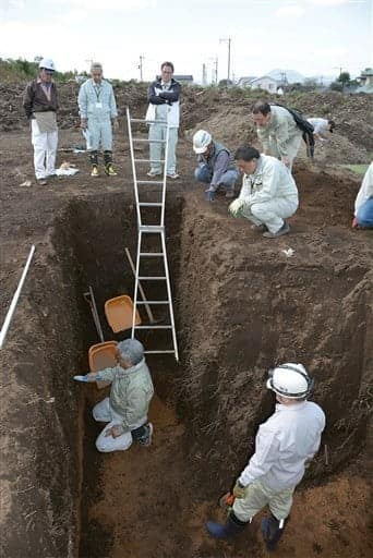 掩体壕跡の発掘調査に立ち会う市職員ら=27日、熊本市東区