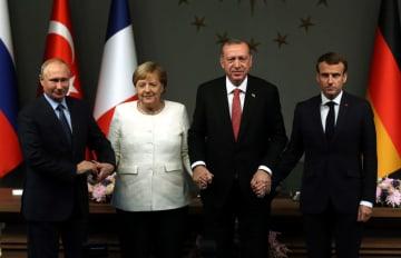 27日、トルコ・イスタンブールで、シリア情勢を巡る首脳会議の後、写真撮影のため並ぶ(左から)ロシアのプーチン大統領、ドイツのメルケル首相、トルコのエルドアン大統領、フランスのマクロン大統領(アナトリア通信提供・共同)