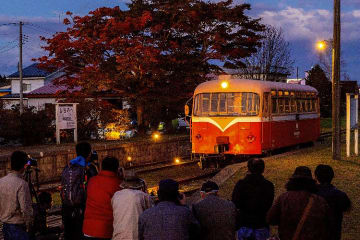 刻々と変わる風景とレールバスを撮影する来場者たち=27日午後5時ごろ、七戸町笊田