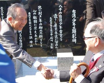 顕彰碑の前で固い握手を交わす、石川公弘会長(左)と李雪峰会長。顕彰碑には石川さんらが創作した3句が記されている
