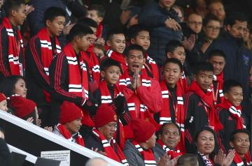 28日、英中部マンチェスターで、サッカーのマンチェスター・ユナイテッドの試合を観戦するタイの少年ら(AP=共同)