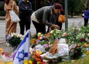 銃撃事件が起きた米ピッツバーグのシナゴーグ近くに花を手向ける人=28日(ゲッティ=共同)