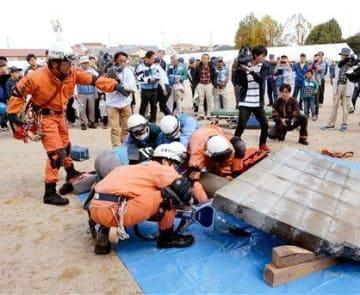益城町の総合防災訓練で、倒壊したブロック塀の下敷きになった人を救助する消防隊員ら=28日、同町