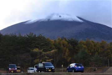 山頂を覆った雲の下が雪で白く染まった岩手山。盛岡地方気象台は初冠雪を観測した=28日午後2時42分、八幡平市平笠・岩手山焼走り国際交流村付近