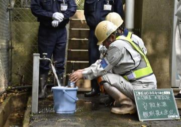 陸上自衛隊むつみ演習場近くの水源で水を採取する調査員=29日午前、山口県萩市