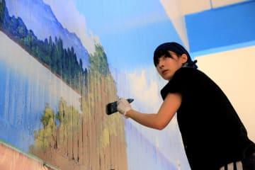 銭湯で陸部分の下絵を塗る勝海さん