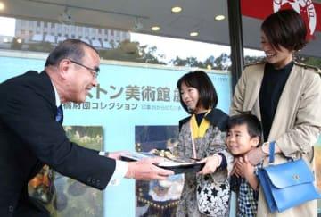 川平副館長(左端)から1万人目の記念品を受け取る原田さん親子
