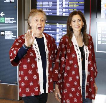 羽田空港に到着し、法被姿でファンに手を振るビートルズの元メンバー、ポール・マッカートニーさん。右は妻ナンシーさん=29日夜