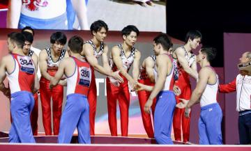 体操世界選手権の男子団体総合決勝で3位となり、2位のロシア代表と表彰式で握手を交わす内村航平(奥右端)ら日本代表=29日、ドーハ(共同)