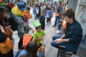 店先で菓子をもらう子どもら。まちは多くの家族連れでにぎわった=岐阜市美殿町