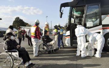 中国電力島根原発の避難訓練で、岡山県に避難するためバスに乗り込む人たち=30日午前、松江市