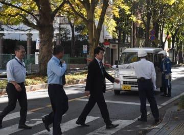横断歩道の前でドライバーに一時停止を呼び掛ける警察官ら(右奥)=29日午後、宇都宮市本町