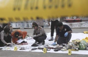 回収された墜落機乗客の所持品を調べる警官=30日、ジャカルタ(AP=共同)