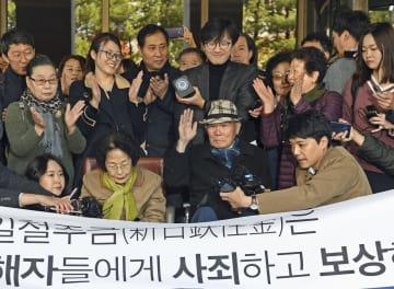 韓国徴用工訴訟で日本企業に賠償を命じた判決が確定し、支援者らから拍手を送られる原告の李春植さん(手前右から2人目)=30日、韓国最高裁前(共同)