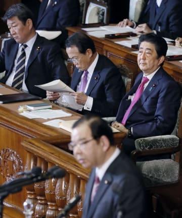 衆院本会議で共産党の志位委員長(手前)の質問を聞く安倍首相(奥右)=30日午後