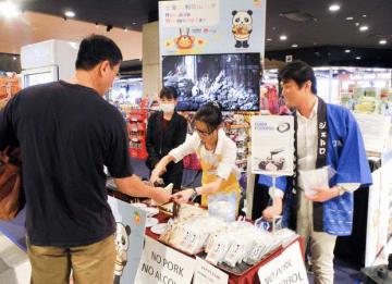 北海道・和歌山フェアでは、チョコレートや黒糖のソースをかけたごま豆腐や、魚の練り物の「ほねく」などを試食販売した=29日、クアラルンプール(NNA撮影)