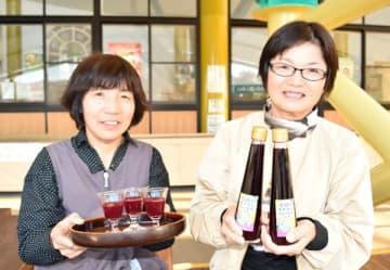 【度会町産のブルーベリーから作った飲む酢を紹介する福井さん(右)と中西さん=度会町大野木で】
