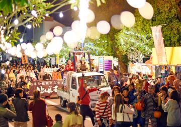木々のライトアップやバーナーの光に包まれる中、パレードする人たち=30日夜、佐賀市の中央大通り(撮影・米倉義房)