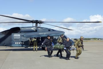 救助訓練で、航空自衛隊のヘリコプターから搬送される米軍のパイロット=31日午前、青森県の米軍三沢基地