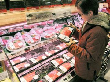 オーストラリア産の牛肉を手に取る客=東京都