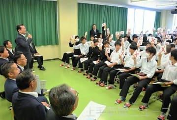 県議の○×式のクイズに札を挙げて答える生徒