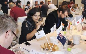 10月11日に行われた「サケ・セレクション」の審査で、出品された日本酒の味を確かめる審査員=三重県鳥羽市