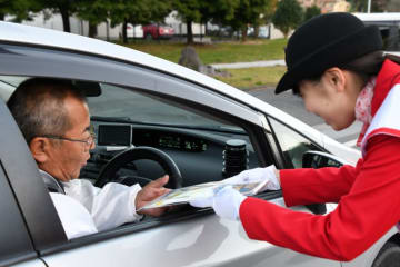 運転者に早めの点灯を呼び掛ける一日署長の金野茜さん(右)