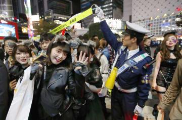 ハロウィーン当日を迎え、東京・渋谷駅前のスクランブル交差点に集まった仮装した若者ら。平日にも関わらず大勢集まり、警察官が交通整理などの対応に追われた=31日夜