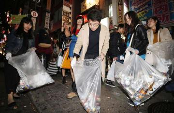 ハロウィーンで大混雑した東京・渋谷でごみを拾う大学生ら=1日未明