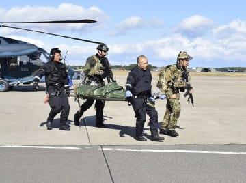 救出したパイロットを搬送する米兵と自衛隊員=31日午前、三沢基地