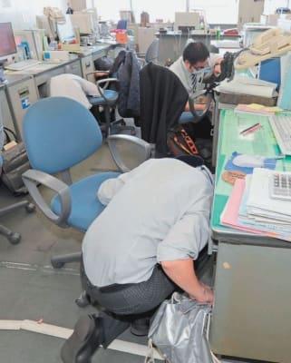 机の下に身を隠す県防災局の職員=1日午前、県庁