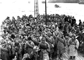 1946年12月、シベリアからの帰還第1船「大久丸」の甲板にたたずみ、上陸を待ちわびる復員兵ら=京都・舞鶴港