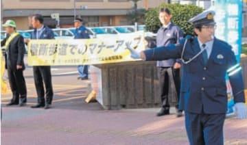通行車両を止め、道路を渡る歩行者を誘導する警察官ら
