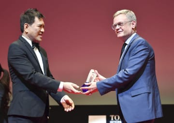 ミカエル・アース監督の「アマンダ」が最高賞を受賞し、トロフィーを受け取るローラン・ピック駐日フランス大使(右)=2日午後、東京都港区