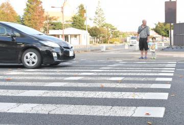 横断歩道を渡ろうと、車が通過するのを待つ親子=10月30日、水戸市内