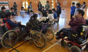 指導員の勝山博行さん(右)の話を聞きながら卓球バレーを楽しむ児童たち=常総市大輪町