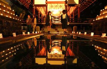 学生たちの手で彩られた境内。拝殿が水鏡に映り込み、幻想的な雰囲気に包まれた(2日午後5時55分、草津市草津4丁目・立木神社)