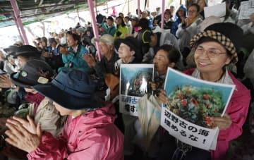 米軍キャンプ・シュワブゲート前での抗議集会で、プラカードを掲げる人たち=3日午前、沖縄県名護市