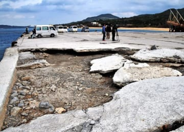 台風の影響でコンクリート舗装が剥がれ、一部路盤がむき出しになっている本部港塩川地区=2日午前