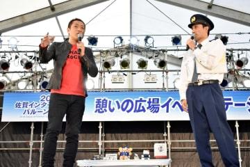 ニセ電話詐欺の防犯を呼び掛けるはなわさん(左)と宮地巡査部長=佐賀市のバルーンフェスタ会場