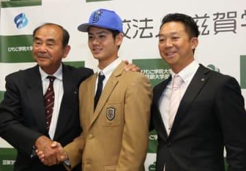 吉田スカウト本部長(左)と握手する宮城投手(中央)=東近江市建部北町・滋賀学園高