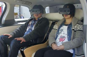 自動運転車内でゴーグル型端末を着け、VRを活用した観光案内を体験する実証実験参加者=3日、長野県飯田市
