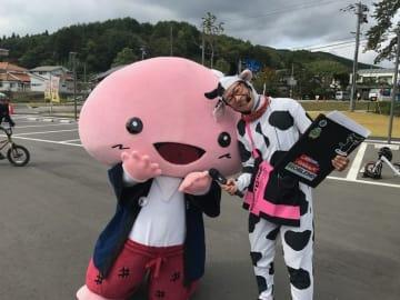 葛尾村マスコットキャラクター「しみちゃん」と親交を深めるMC牛