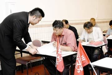 大内学編集長(左)の指導を受けながら原稿の校正作業を体験した鉄道ファン=11月3日、福井県の敦賀市立博物館